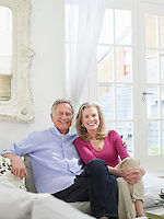 Senior couple sitting on sofa portrait