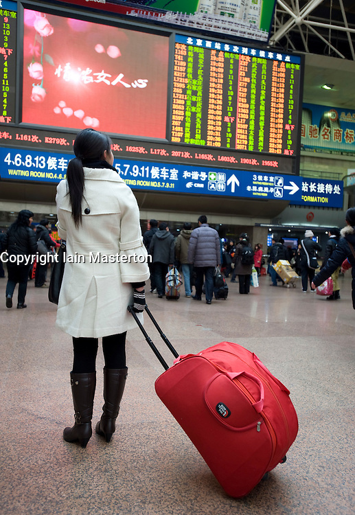 Young Chinese woman travelling home for Chinese New Year January 2009 at Beijing West Raiway Station 2009