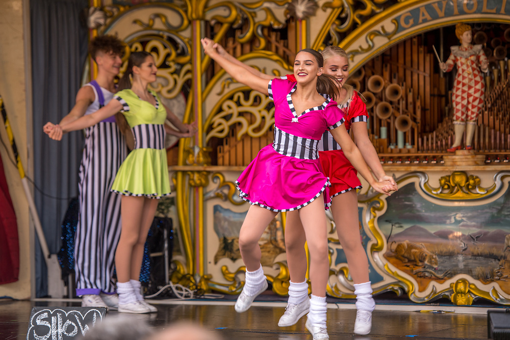 Dancers in colorful costumes dance with joy on top of fairground organ, Masham, North Yorkshire, UK
