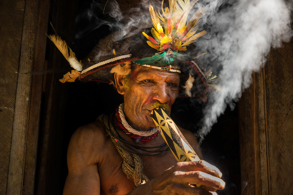 A Huli wigmen chief smokes a pipe, Tari, PNG.