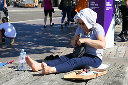 © Licensed to London News Pictures. 23/08/2019. London, UK. A woman covers her head with a towel on a warm and sunny day in Granary Square, King's Cross, London. According to the Met Office, the temperatures are forecast to increase to 30 degrees celsius for the bank holiday weekend.  Photo credit: Dinendra Haria/LNP