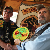 RAY VAN DUSEN/BUY AT PHOTOS.MONROECOUNTYJOURNAL.COM<br /> Larry Taylor, right, accepts patches from Howard Ausborne signifying his membership in the 8-ball chapter of In Country Vietnam Motorcycle Club during a ceremony at Ausborne's home.