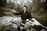Fly fishing guide rows a drift boat on Michigan's Pere Marquette River during the fall salmon run.