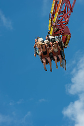 © Licensed to London News Pictures. 13/06/2014. Isle of Wight, UK.   Festival goers fly through the air against a sunny blue-sky on a fairground ride at the Isle of Wight Festival 2014.  Atmosphere at Isle of Wight Festival 2014.   The Isle of Wight festival is an annual music festival that takes place on the Isle of Wight. Photo credit : Richard Isaac/LNP