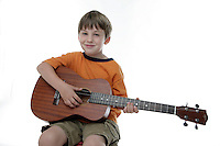 20 July 2008:  Back to School with grammar school Lytle brothers in Huntington Beach, CA.  Matthew Lytle age 6 holding ukulele in the studio on white seamless paper silo.