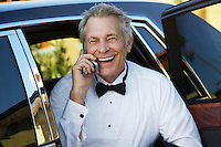 Middle-aged man talking on mobile phone in open door of limousine, portrait