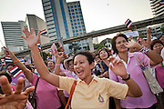 "Apr. 2, 2010 - BANGKOK, THAILAND: A woman wearing a yellow shirt, the official color of the Thai monarchy, joins ""Pink Shirts"" in calling for the ""Red Shirts"" to get out of Bangkok. Thousands of ""Pink Shirts,"" who claim to be neither ""Red Shirts"" nor ""Yellow Shirts"" nicknames for Thailand's dueling political forces, gathered in Lumpini Park in central Bangkok Friday evening to call for ""peace in the land,"" a play on the Red Shirts slogan, ""Red in the Land."" The ""Pink Shirts"" represented educators, business people and people in the tourist industry, all of which have been hurt by the ongoing political protests that have disrupted life in the Thai capital. The ""Pink Shirts"" stressed their loyalty to His Majesty Bhumibol Adulyadej, the King of Thailand, and chanted for the Red Shirts to ""Get Out!"" of Bangkok.    PHOTO BY JACK KURTZ"