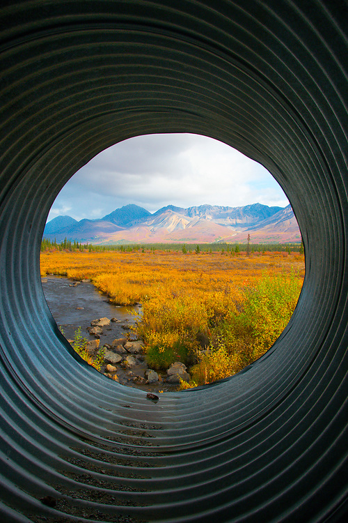 A pristine vantage point from inside a large road culvert overlooking a stunning fall,landscape.