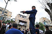 Israel, Haifa, Wadi Nisnas, Young Arab Boy points a hand gun at the crowd during the Holiday of holidays festival, celebrating Hanuka-Christmas-Ramadan December 2009