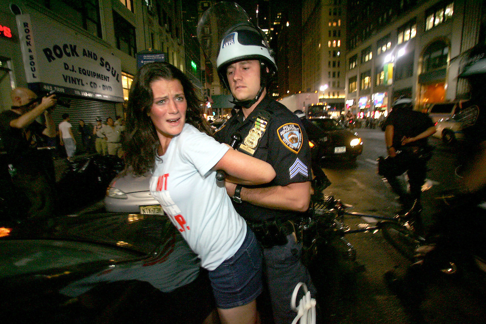 "epa000263640 A New York City Police officer arrests a demonstrater as her bicycle lies on the street as thousands of bicyclists staged a ""Critical Mass"" protest and clogged Seventh Ave. and 34th St. in front of Madison Square Garden in New York City, Friday, 27 August 2004. Both security and protesting has increased steadily in the days leading up to the 30 August start of the Republican National Convention at New York City's Madison Square Garden.  EPA/ANDREW GOMBERT"