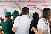 26 JUNE 2011 - CHIANG MAI, THAILAND: People look for their polling place at the Chiang Mai voting station during absentee voting in the Thai national election Sunday. Absentee voting was Sunday, July 26 in Thailand's national election. The regular voting is Sunday July 3. In Chiang Mai, center of the powerful Red Shirt opposition movement and their legal party Pheua Thai, turnout was heavy despite a steady rain. Thailand's democracy will be tested in the election, which is the most bitterly fought contest in Thai political history. The Pheua Thai represents people loyal to fugitive former Prime Minister Thaksin Shinawatra, ousted by a military coup in 2006. The ruling Democrats have governed Thailand in one form or another nearly continuously since 1932. Pre-election polls show Pheua Thai leading but not by enough to rule without forming a coalition with smaller parties.   PHOTO BY JACK KURTZ