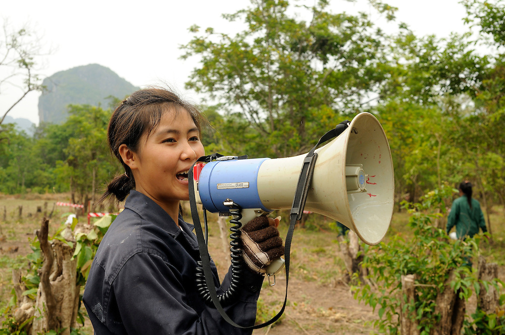 "Mines Advisory Group female Technician, Douangmala Suansython, age 21, warns villagers to clear the area before the ladies team set of a controled demolition of 76 cluster bombs.  ..Laos was part of a ""Secret War"", waged within its borders primarily by the USA and North Vietnam.  Many left over weapons supplied by China and Russia continue to kill.  However, between 90 and 270 million fist size cluster bombs were dropped on Laos by the USA, with a failure rate up to 30%.  Millions of live cluster bombs still contaminate large areas of Laos causing death and injury.  The US Military dropped approximately 2 million tons of bombs on Laos making it, per capita, the most heavily bombed country in the world. ..The women of Mines Advisory Group (MAG) work everyday under dangerous conditions removing unexploded ordinance (UXO) from fields and villages...***All photographs of MAG's work must include (either on the photo or right next to it) the credit as follows:  Mine clearance by MAG (Reg. charity)***."