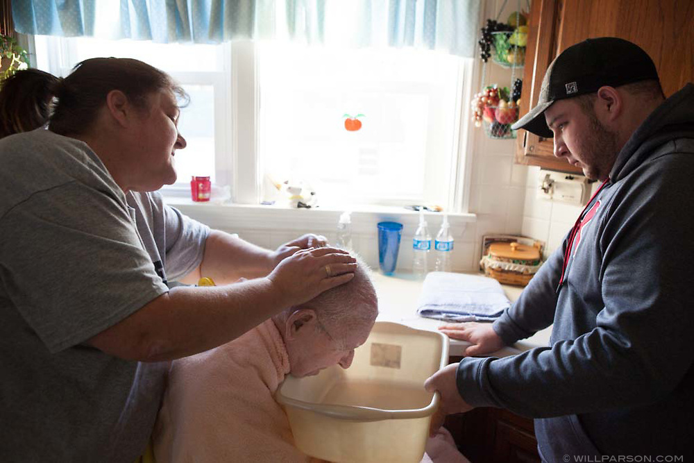 Missy Parsons washes her father Sam Parsons' hair with the help of her son K.B. Brozak in the kitchen of Sam and his wife Sue Parsons' home in Guysville, Ohio. Sam Parsons has been incapacitated by ALS since 2009. His wife initially served as his primary caretaker, but Sue's own health problems starting in November of 2011 have caused her to seek more help from relatives and a neighbor to take care of her husband.