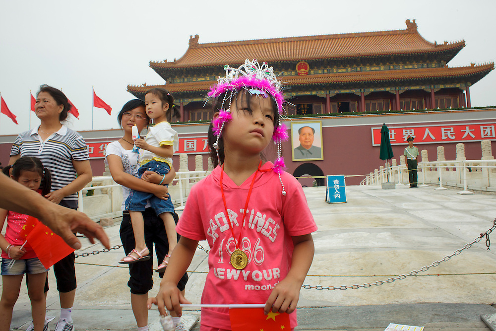 A chinese girl poses for photo in front of Mao Zedong portrait hang on the FOrbidden City's facade