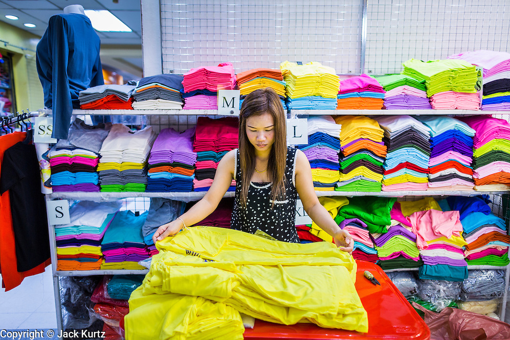 06 JUNE 2013 - BANGKOK, THAILAND:     A vendor folds tee shirts she sells wholesale in Bobae Market in Bangkok. Bobae Market is a 30 year old market famous for fashion wholesale and is now very popular with exporters from around the world. Bobae Tower is next to the market and  advertises itself as having 1,300 stalls under one roof and claims to be the largest garment wholesale center in Thailand.       PHOTO BY JACK KURTZ
