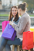 Female friends with shopping bags communicating while sitting on bench