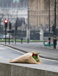 © Licensed to London News Pictures.23/03/2017.London, UK. A floral tribute is left in site of Carriage Gate outside Parliament in Westminster, London, the day after a lone terrorist killed 4 people and injured several more, in an attack using a car and a knife. The attacker managed to gain entry to the grounds of the Houses of Parliament, killing one police officer.Photo credit: Peter Macdiarmid/LNP