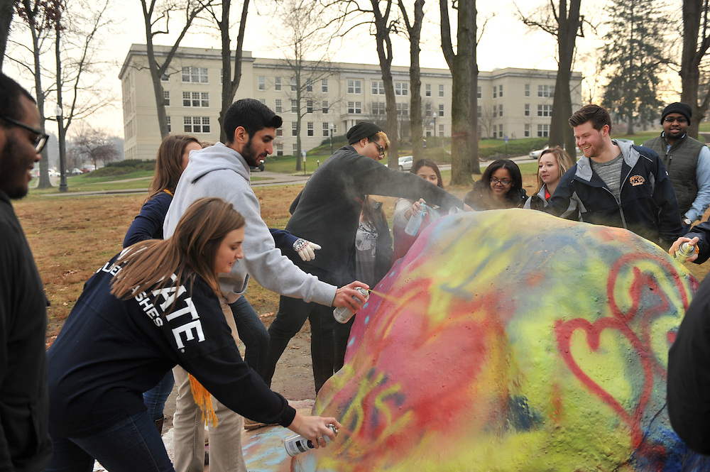 """Students paint """"The Rock"""" on Front Campus along East Main Street. The rock has been a Kent State tradition ince the 1930s. It was moved to it's current location in 1972."""
