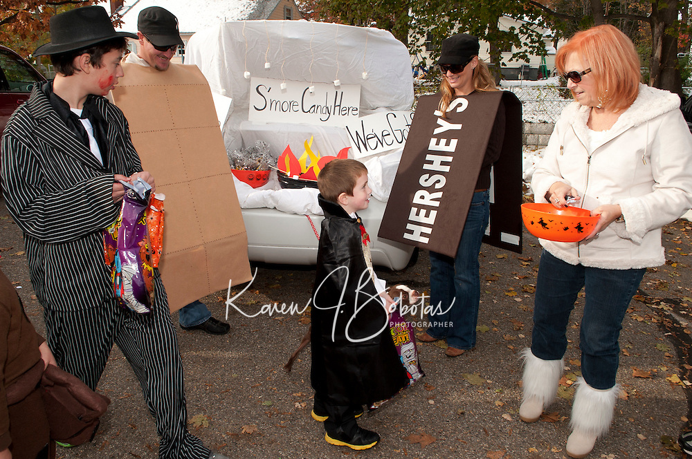 """A steady stream of students from the Holy Trinity School enjoyed collecting candy from the Smore's vehicle decorated by Mike Dion as the graham cracker, Bianca Dion as the Hershey Bar, Nance Palermo as a Marshmallow along with their dog Rex during the """"Trunk or Treat"""" Halloween party Monday afternoon.  (Karen Bobotas/for the Laconia Daily Sun)"""