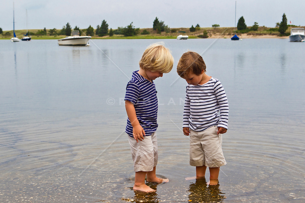 two boys exploring the water in a bay