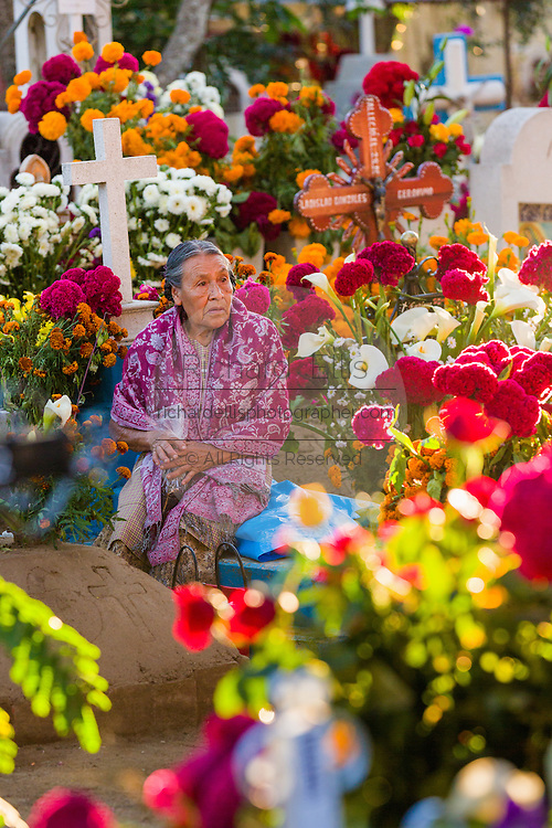 An elderly woman reflects at the gravesite of her deceased husband decorated with flowers at the San Antonino Castillo cemetery for the Day of the Dead Festival known as Día de Muertos on November 3, 2013 in San Antonino Castillo Velasco, Oaxaca, Mexico.