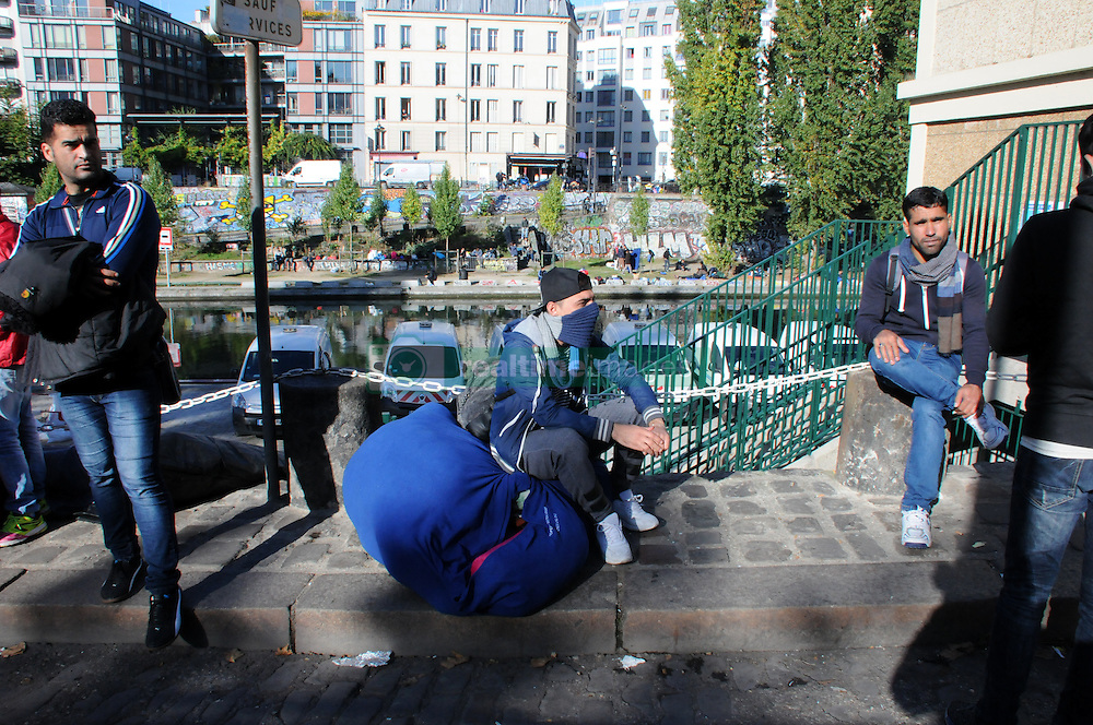 """A migrant stands at the Canal Saint-Martin, near the Jaures and Stalingrad metro stations, in northern Paris, France, on October 31, 2016, during a police operation aiming at a future evacuation of a migrant camp. An operation of """"administrative control"""" was underway on early October 31 in the Jaures/Stalingrad quarter before a future evacuation, whose date has not yet been set, according to a police source. The makeshift camp on the outskirts of the 10th and 19th arrondissements in the north of the capital numbers today 2,500 people, according to the City of Paris. Photo by Alain Apaydin/ABACAPRESS.COM"""