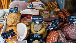 Deli stall detail with sausage and meats at indoor market , Markethalle Neun, Kreuzberg, Berlin, Germany.
