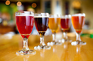 """The Cascade Brewing Barrel House in the Southeast neighborhood of Portland, Oregon specializes in barrel-aged sour beers.  Pictured here is a line-up of tasters.  At $2 per 2 oz., this is a great way to sample the diverse offerings of Northwest traditional, hand-crafted and barrel-aged sour beers.  From left to right: """"Nightfall"""" (blackberry sour); """"Sang Rouge"""" (NW style sour red); """"Spring Gose"""" (traditional german salted wheat beer flavored with sea salt, two culinary lavenders, chamomile and lemon peel; """"Kriek"""" (one of the oldest styles of sour fruit beers containing bing and sour pie cherries); and """"Beck Berry"""" ( another cherry beer)"""