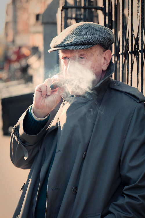 A man in a trenchcoat and cap stands on a street in the East Village of New York smoking a cigar.