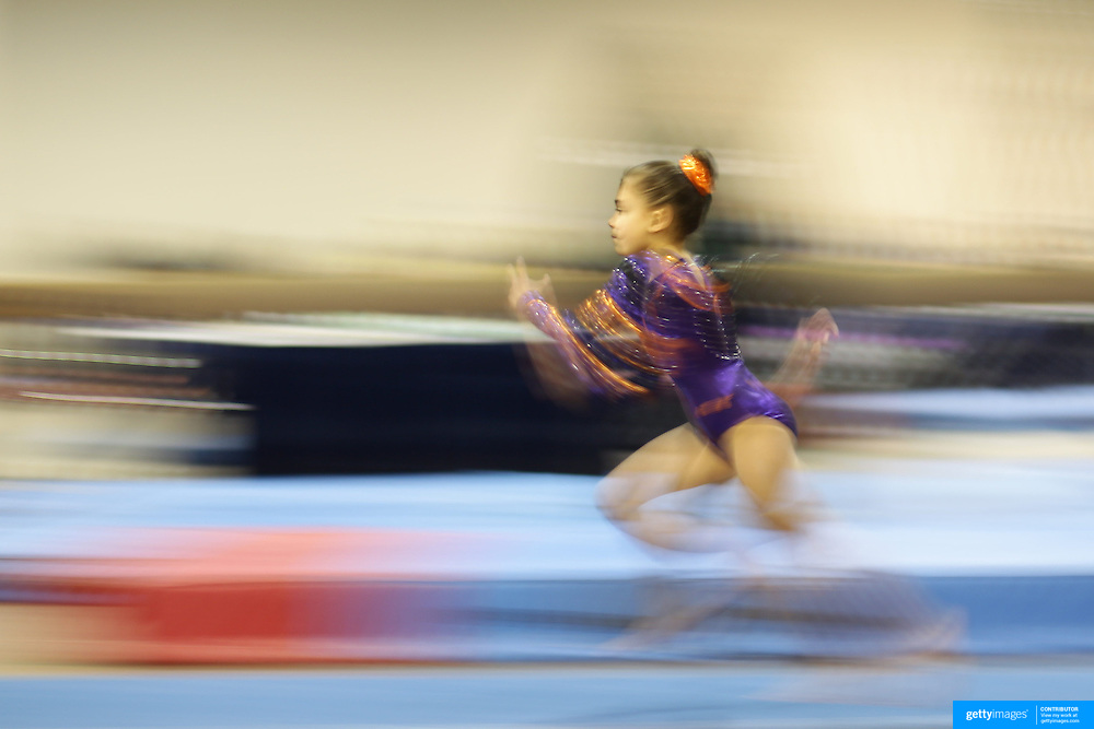 A blur of motion as a young gymnasts sprints towards the vault during competition at the 21st American Invitational 2014 competition at the XL Centre. Hartford, Connecticut, USA. USA. 31st January 2014. Photo Tim Clayton