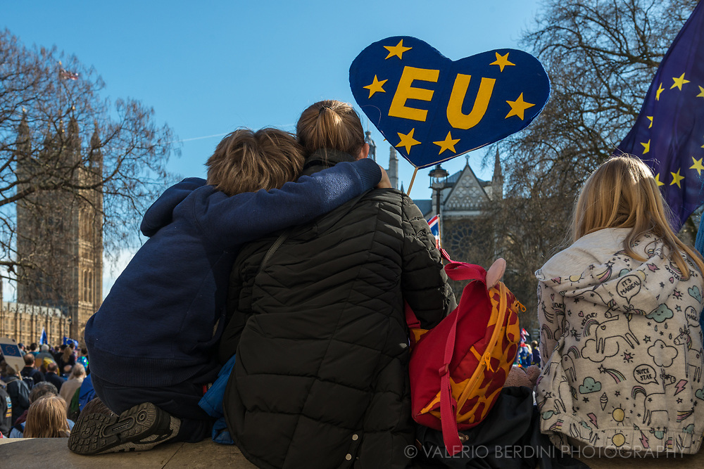 A family listens to the talk by pro EU politicians in Parliament square.