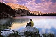 Idaho. Sawtooth NRA. Hiker taking in some sunrise solitude with clouds reflecting on Upper Cramer Lake.  MR