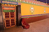 A Tibetan monk finds a quiet place to rest on the roof of the Jokhang in Lhasa, Tibet.