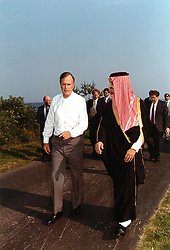 Kennebunkport, Maine - August 16, 1990 -- United States President George H.W. Bush walks along the driveway of his home in Kennebunkport, Maine with Foreign Minister Prince Saud Al-Faisal of Saudi Arabia on August 16, 1990. They met to discuss the situation in the Persian Gulf. National Security Advisor Brent Scowcroft can be seen behind the President at far left and White House Chief of Staff John Sununu can be seen behind the Prince at far right. Photo by White House/ CNP/ABACAPRESS.COM