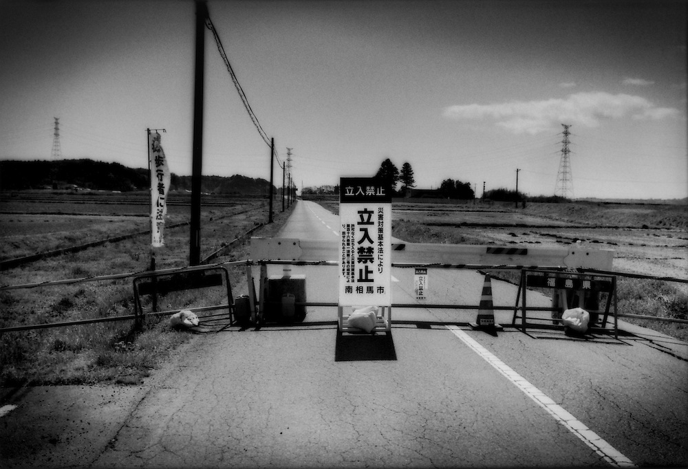 "An unguarded barrier to entry into the 20 km (12.4 miles) nuclear no-entry zone.  Minami Soma, Fukushima Prefecture, Japan.  There are scores of barriers spread around the circumference of the exclusion zone and most are unguarded due to a shortage of police personnel.  The sign reads in Japanese, ""entry forbidden"".  As of midnight 21 April 2011, the Japanese government declared the no-entry zone off-limits under the Disaster Countermeasures Basic Law which gives the police the power to detain anyone entering the zone for up to 30 days and impose a fine of up 100,000 JPY (US$1,200), which was exactly the risk necessary to take to make this photograph.."