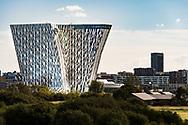 Long-range shot of The Bella Sky Hotel, part of the Bella Center in Copenhagen, against a blue sky on a sunny day in Denmark.