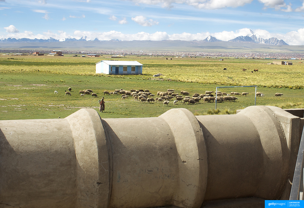 A local indigenous sheep herder walks past a water pipe at The Bolivian Ministry of Water treatment plant at Puchuckollo, Bolivia. The plant is run by state-owned Bolivian water utility EPSAS which manages the water distribution and sanitation services in capital La Paz and neighboring city El Alto.<br /> <br /> <br /> Climate change and the fast diminishing glaciers in the Andes are posing a serious threat to water supplies. Scientists expect that global warming will melt most Andean glaciers in the next 30 years.<br /> &nbsp;La Paz and it's sprawling satellite city El Alto are vulnerable to the effects of climate change and the retraction of the glaciers. Over 2 million people in the region depend heavily on the thawing of Chacaltaya and neighboring glaciers for fresh water. The dams in the highland areas of the Altiplano divide are basically fed by two sources, rainfall and the glaciers, both are suffering from global warming. The declining levels of water in the dams is presenting another problem, contamination and the concentrations of salts, The Bolivian government have launched a number of schemes to help combat the shortage of water and improved water treatment to maintain quality as well as trying to educate and change habits of water usage.<br /> <br /> <br /> Cochabamba, Bolivia, will host the World's People's Conference on Climate Change and the rights of Mother Earth from April 19th to April 22, 2010.