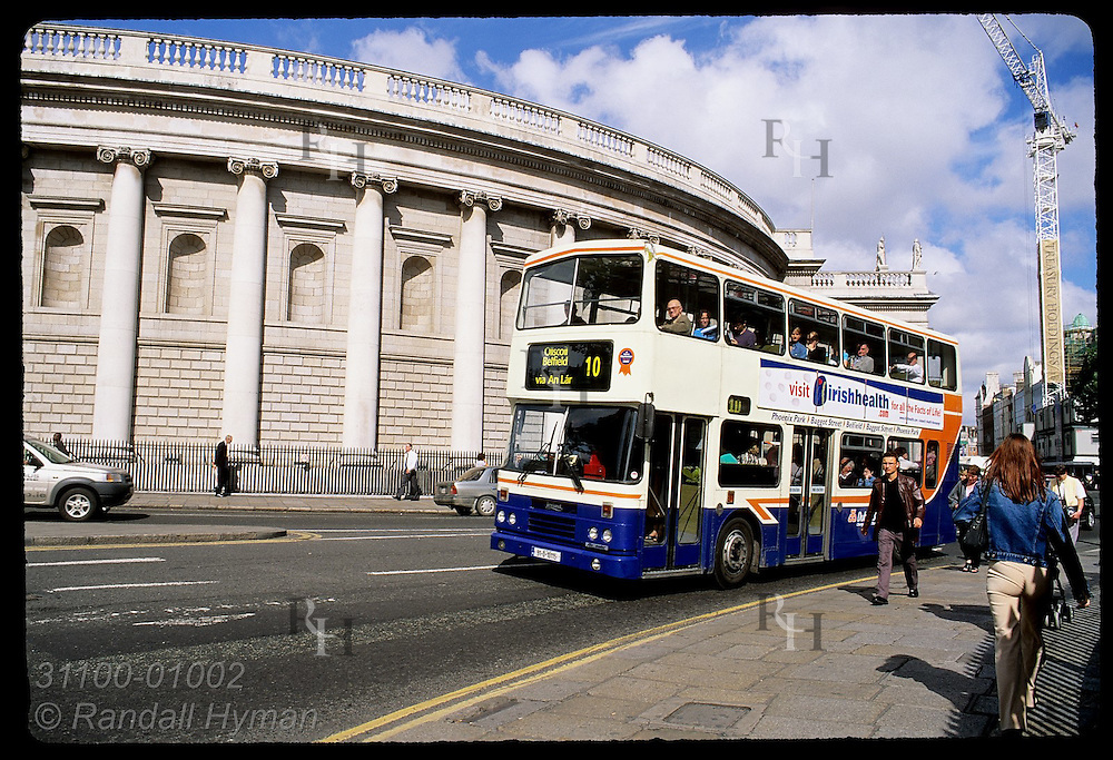 Double-decker bus rushes along busy College Street across from Arts Centre at Trinity College entrance; Dublin, Ireland.