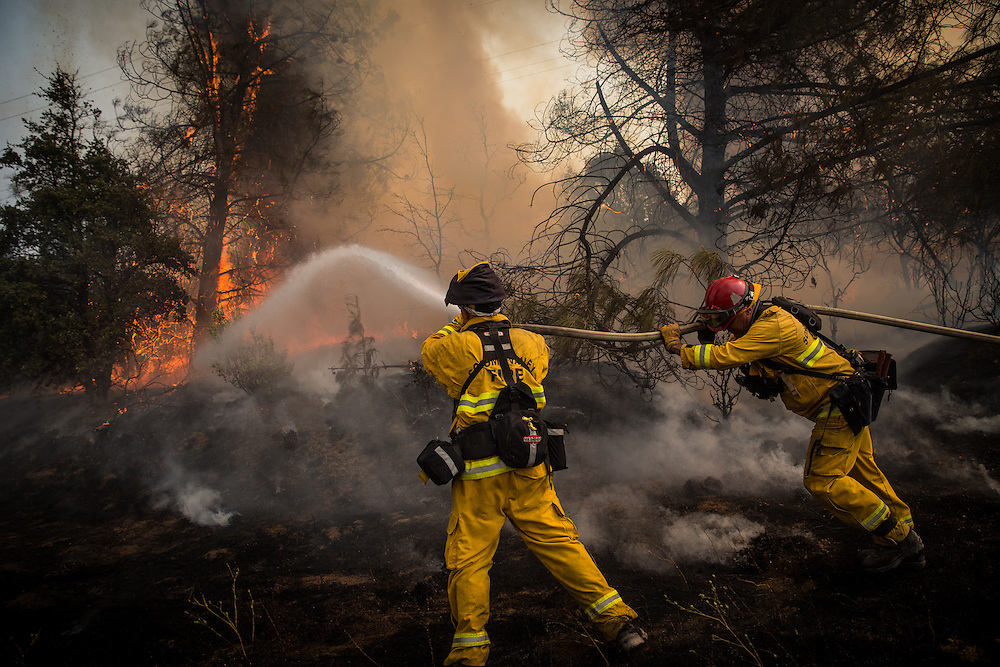 Firefighters battle a spot fire on the Rocky Fire in Lake County, California on July 30, 2015. As of August 5, the fire had consumed 69,600 acres and is one of 23 wildfires burning in California.