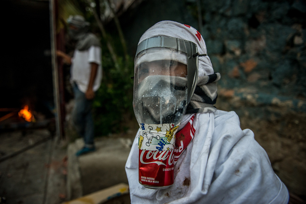 CARACAS, VENEZUELA - MAY 26, 2017:  A young anti-government protester with a homemade gas mask made from a water jug, duct tape and a soda can poses for a portrait while building a road block. Many of the protesters on the front line of clashes with authorities are from the slums surrounding Caracas, and cannot afford to purchase expensive protective gear. Protesters are regularly seen with handmade, or improvised protective gear - swim goggles to keep the tear gas out of their eyes, cheap motorcycle helmets and some have even taken to making artesianal gas masks from plastic soda bottles, and duct taping magazines around their shins, for protection.  PHOTO: Meridith Kohut