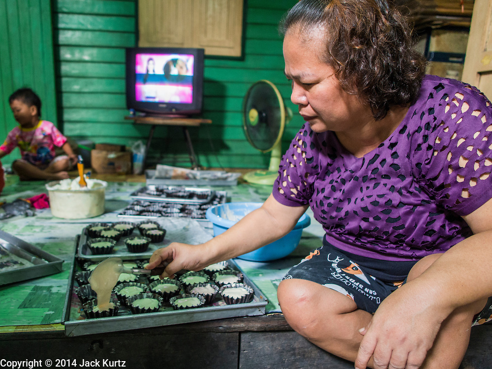 """28 OCTOBER 2014 - BANGKOK, THAILAND: A worker drops batter into cake cups at the Pajonglak Maneeprasit Bakery in Bangkok. The cakes are called """"Kanom Farang Kudeejeen"""" or """"Chinese Monk Candy."""" The tradition of baking the cakes, about the size of a cupcake or muffin, started in Siam (now Thailand) in the 17th century AD when Portuguese Catholic priests accompanied Portuguese soldiers who assisted the Siamese in their wars with Burma. Several hundred Siamese (Thai) Buddhists converted to Catholicism and started baking the cakes. When the Siamese Empire in Ayutthaya was sacked by the Burmese the Portuguese and Thai Catholics fled to Thonburi, in what is now Bangkok. The Portuguese established a Catholic church near the new Siamese capital. Now just three families bake the cakes, using a recipe that is 400 years old and contains eggs, wheat flour, sugar, water and raisins. The same family has been baking the cakes at the Pajonglak Maneeprasit Bakery, near Santa Cruz Church, for more than 245 years. There are still a large number of Thai Catholics living in the neighborhood around the church.   PHOTO BY JACK KURTZ"""