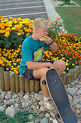 Skateboarder age 15 eating fast food hamburger by flowers.  South Dakota USA