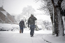 © Licensed to London News Pictures. 10/12/2017. Tring, UK. Dog walkers in heavy snow fall in the town of Tring in Buckinghamshire, England as parts of the south east of England are blanketed with snow for the first time this winter. Photo credit: Ben Cawthra/LNP