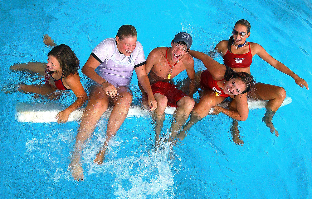 From left, City of Longmont lifeguards Kelly Schneider, 17, Lindsay Walker, 17, Adam Tway, 16, Kendra Vannorsdek, 17, and Rachel Tart, 16, topple over while posing for a portrait on a boogie board in Sunset Pool, July 14, 2007.  The lifeguards will be competing in the Colorado Parks and Recreation Association's Lifeguard Games at Hyland Hills Water World on Sunday, July 15. (Daily Times-Call, Bradley Wakoff)
