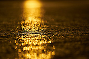 Sunset Bokeh reflections on a flat sea at Gerroa, NSW, Australia