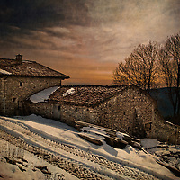 A winter scene with snow of an old house at dusk