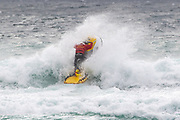 RNLI Lifeguard crashes through the waves to carry out a rescue during the Boardmasters Longboard Pro at Fistral Beach, Newquay, Cornwall, United Kingdom on 10 August 2019.