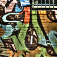 Urban alley scene with multicolored graffiti and barred window.