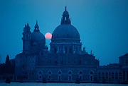 ITALY, VENICE Canal Grande or Grand Canal with the sun  setting behind Santa Maria della Salute, church built in the 17thC by Longhena