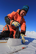 Marine chemist Agneta Fransson (NPI) measures temperature of ice core atop frozen fjord; Kongsfjord, Svalbard, Norway.